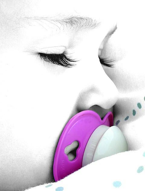 Baby mit lila Schnuller in...