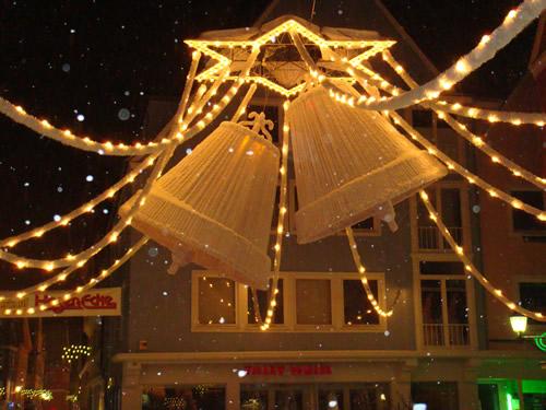 Große, hell leuchtende Glocken hängen über dem Weihnachtsmarkt